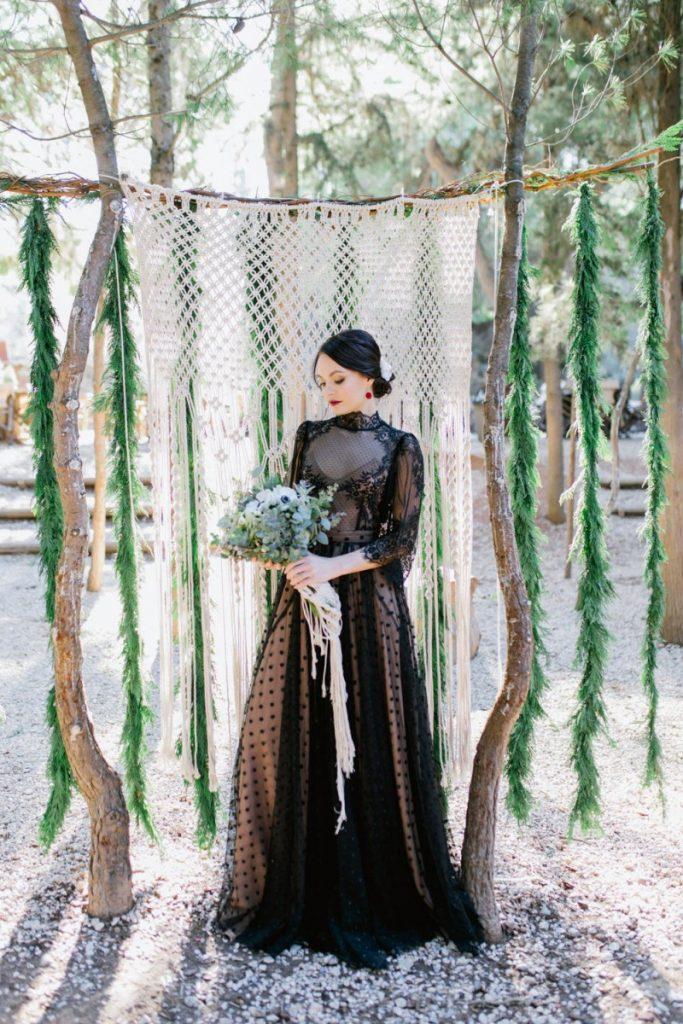 Bride in black in the forest winter wonderland