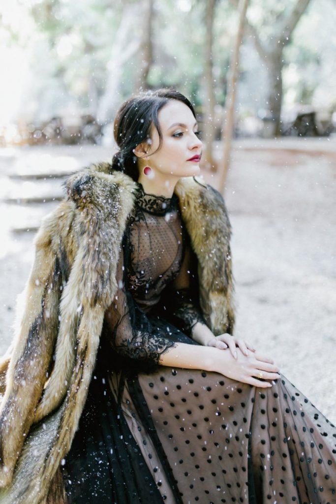 Bride sitting in the black dress in the winter forest wonderland