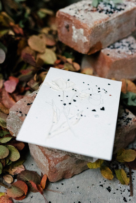 delicate flower on a paper and old brick