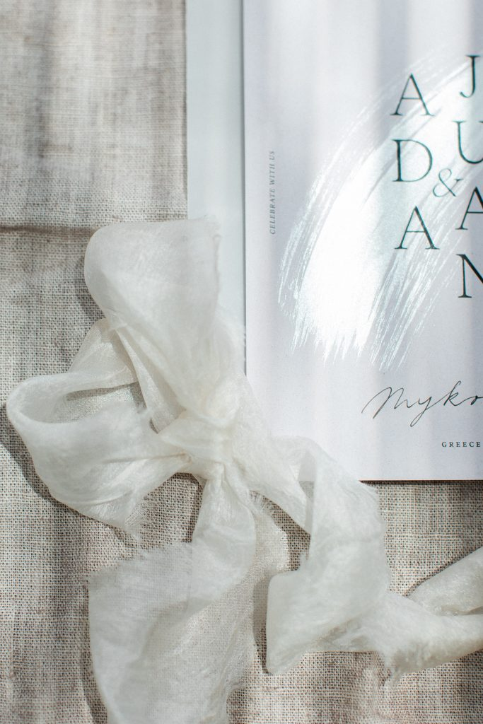 Love Story in Mykonos stationery flatlay with silk ribbon