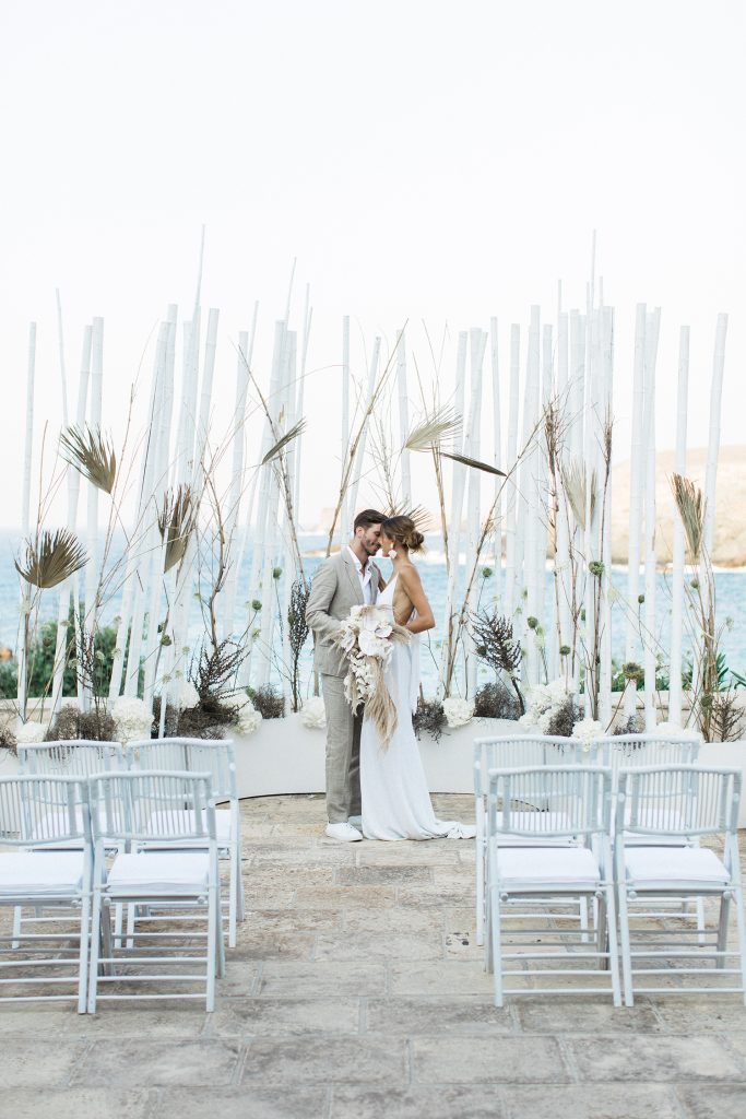 Couple Love Story in Mykonos getting married in Greece in front of the bamboo backdrop