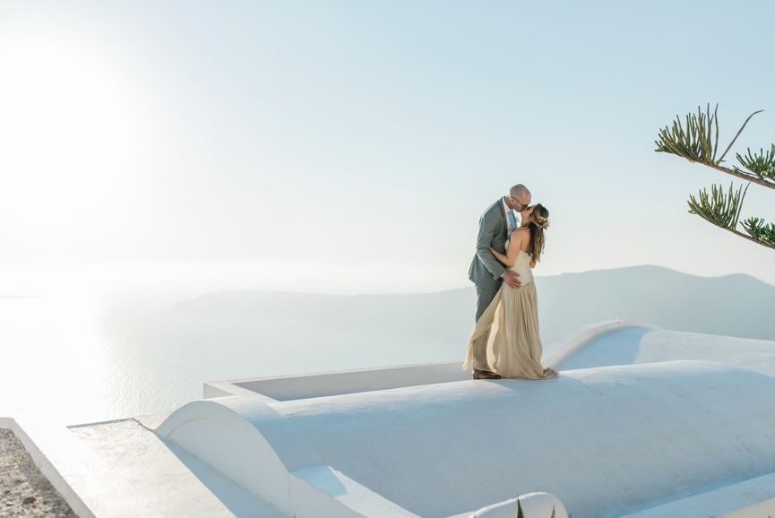 Hellenic Chic Elopement couple kissing on the rooftop in Santorini
