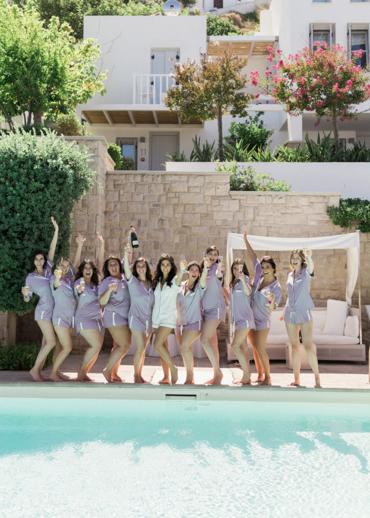 Group of girls having fun by the pool for wedding week in Greece