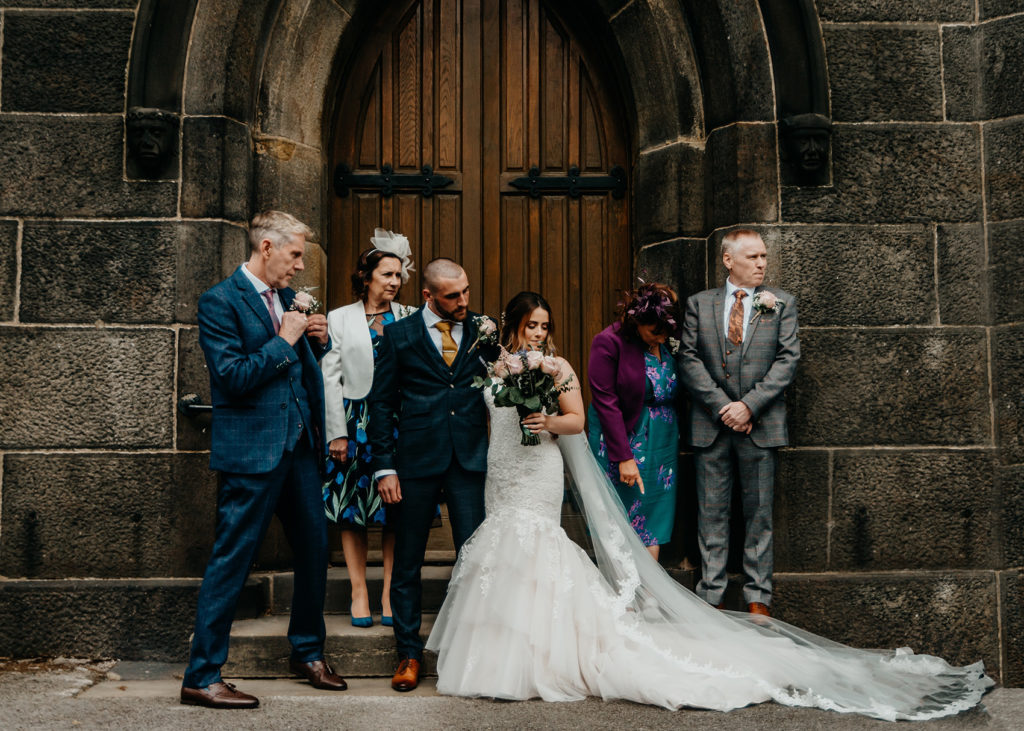 Family portrait in front of the church doors with smart dressed parents