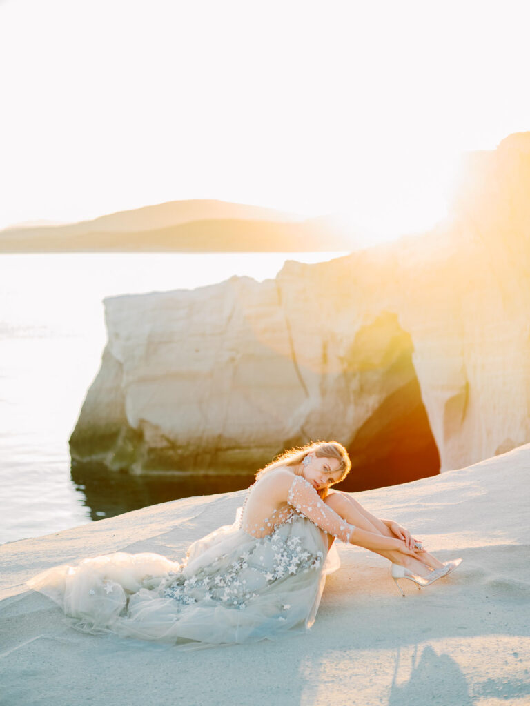 Bride sitting on the cliffs at Milos beach