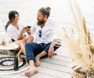 Couple sitting on the pier for t he most magical engagement shoot that ended with a sailing yacht ride