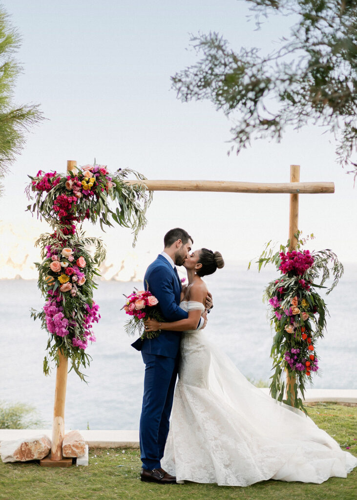 couple kissing under the arch