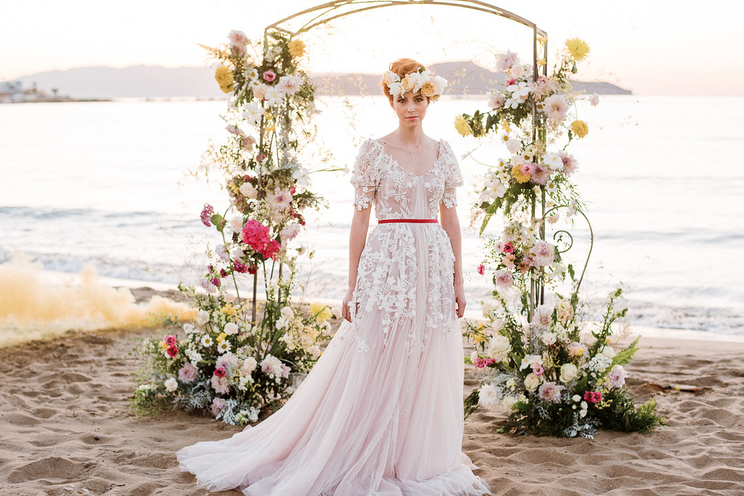 Romantic bride standing at the arch for wedding ceremony and reception ideas from the sunny island of Crete.