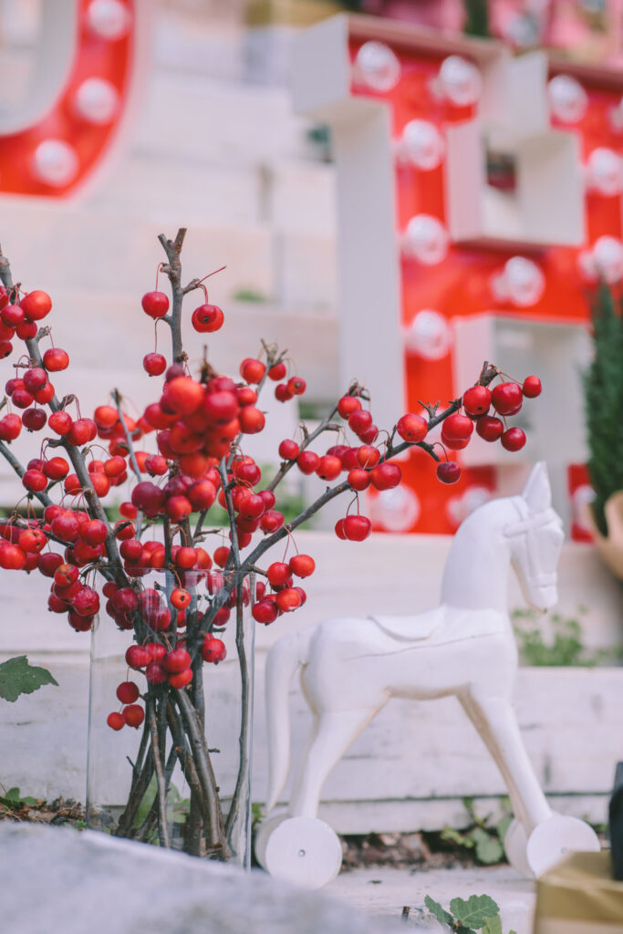 Christmas décor with red berries and white toy horse