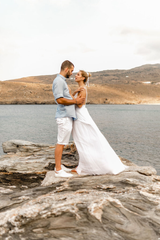 Bride and Groom hugging on the rocks by the sea