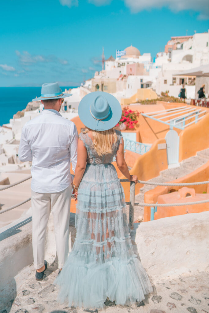 Instagram Influencer couple in Santorini looking over the cluster of white houses