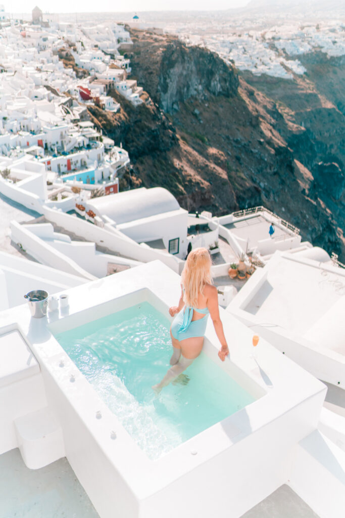 Girl Instagram Influencer in the pool in Santorini overlooking the town