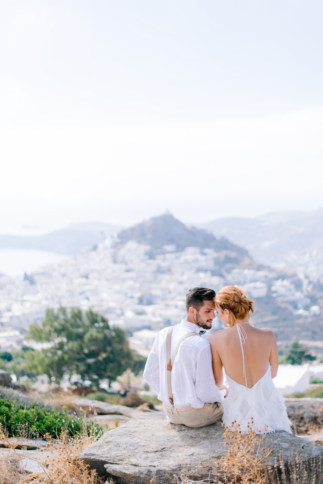 Couple sitting with the view of Ios Utterly Romantic Elopement