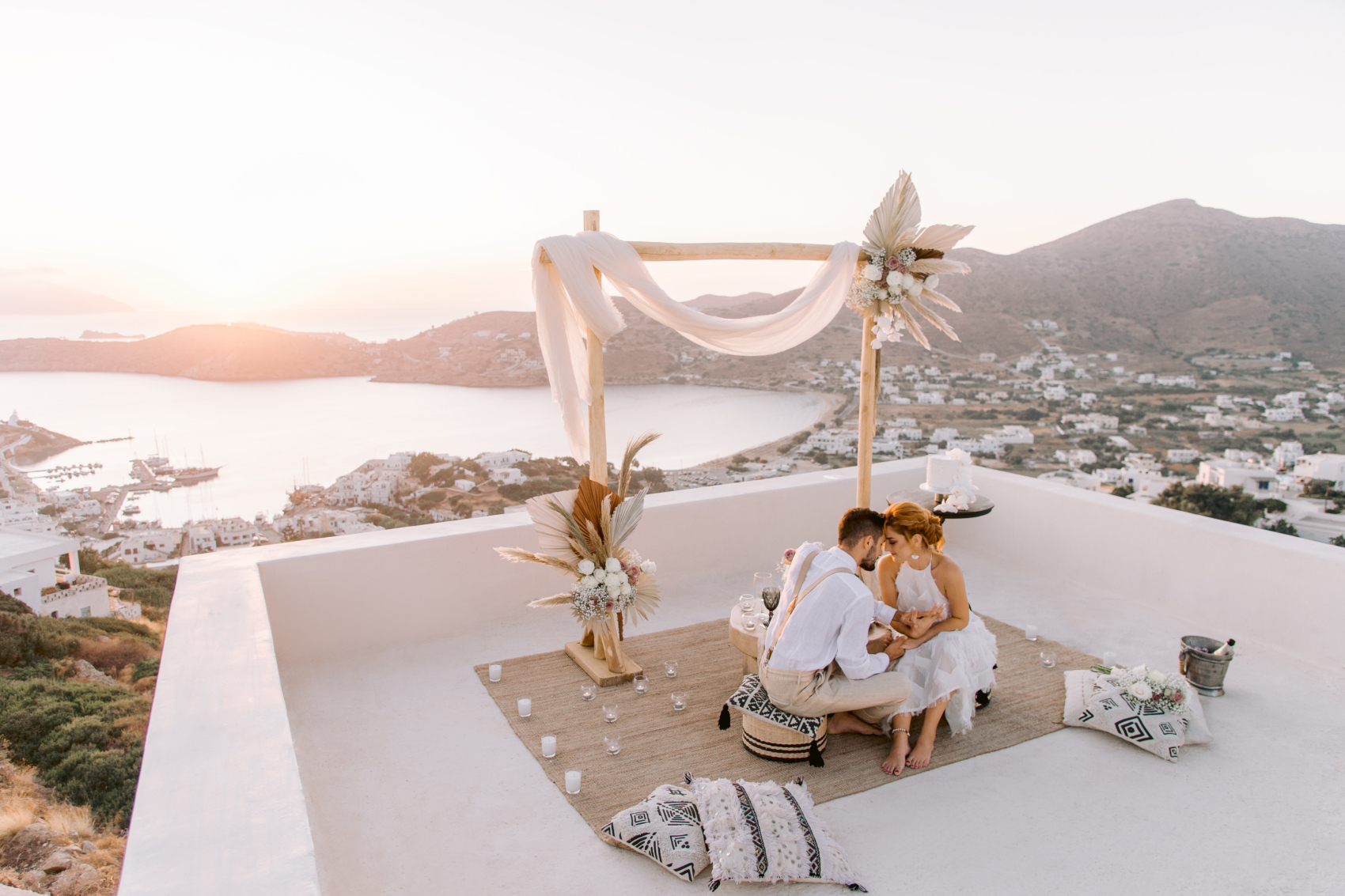 Couple sitting in Ios with a view of the sunset at their Utterly Romantic Elopement