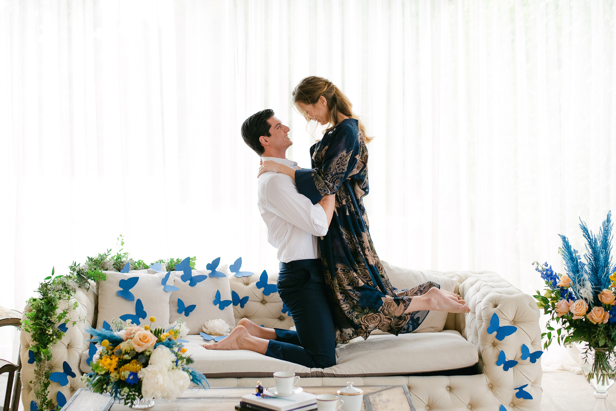 True Blue Luxury Wedding Inspiration Groom lifting the bride with joy on the couch decorated with butterflies