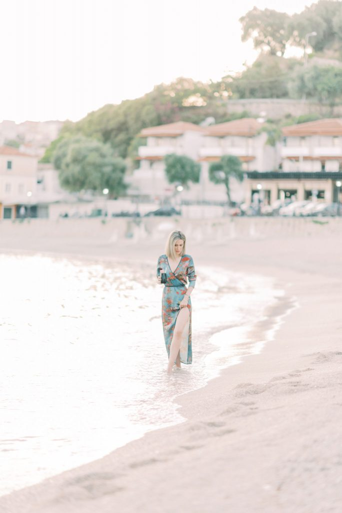 Girl walking down the beach at sunset